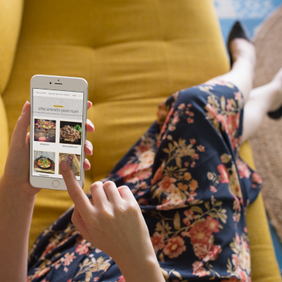 silver-iphone-mockup-of-a-girl-lying-on-a-mustard-sofa-a21505